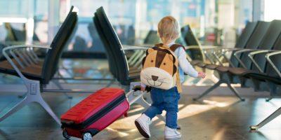 Kinder, die zusammen reisen, am Flughafen warten, um das Flugzeug zu besteigen