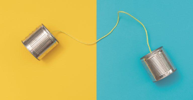 Blechdose auf gelbem und blauem Papierhintergrund telefonieren