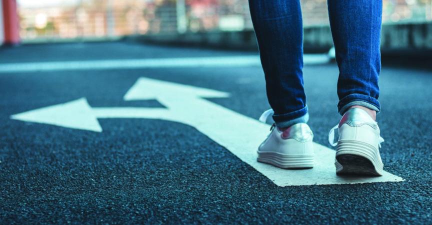 Weibliche Beine mit Jeans und weißen Turnschuhen.
