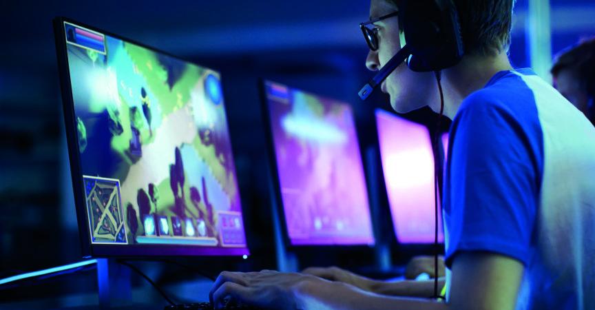 Team von professionellen eSport-Gamern, die in einem kompetitiven MMORPG/Strategie-Videospiel auf einem Cyber-Games-Turnier spielen. Sie sprechen miteinander in Mikrofone. Arena sieht cool aus mit Neonlichtern.
