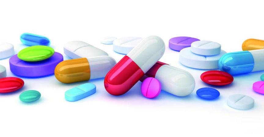 Anhäufung verschiedenster farbiger Medizinpräparate, Kapseln und Pillen auf weißem Untergrund