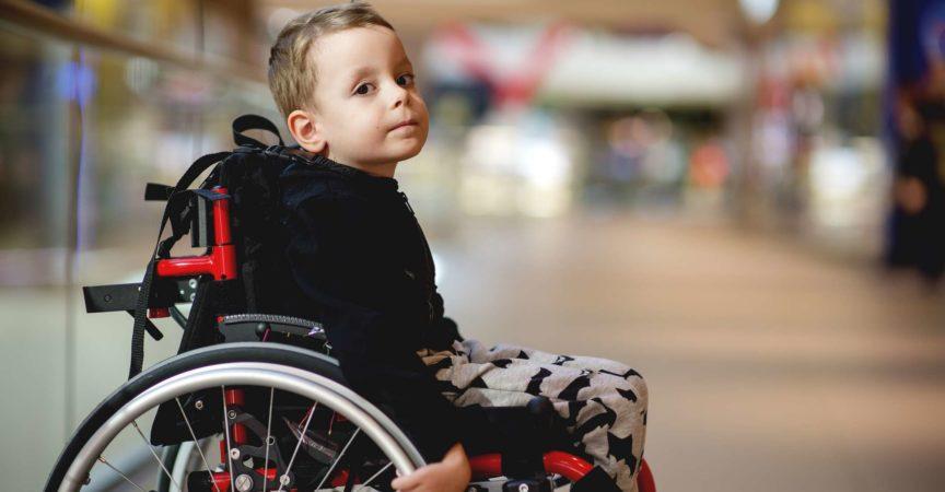 Netter kleiner Junge im Rollstuhl im Einkaufszentrum