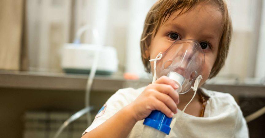 Kleines Kind, das Asthmabehandlung erhält und zu Hause einen Inhalator verwendet.
