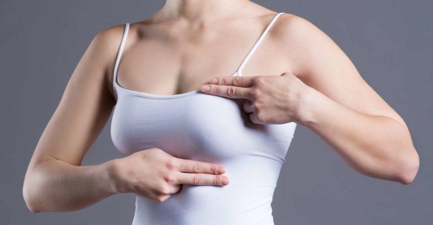 Brusttest, Frau untersucht ihre Brüste auf Krebs, Herzinfarkt, Schmerzen im menschlichen Körper auf grauem Hintergrund