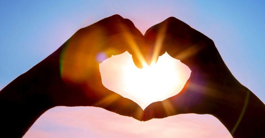 Ein DSLR-Foto von Händen, die mit der Sonne eine Herzform mit schönen Sonnenstrahlen im Inneren bilden. Hintergrund des blauen Himmels. Platz für Kopie.