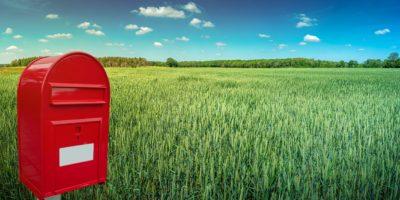 Großer roter moderner Briefkasten mit weißem leerem Notizraum für Adresse steht im Freien vor schönem Landschaftshintergrund mit grünem Weizenfeld und blauem Himmel.
