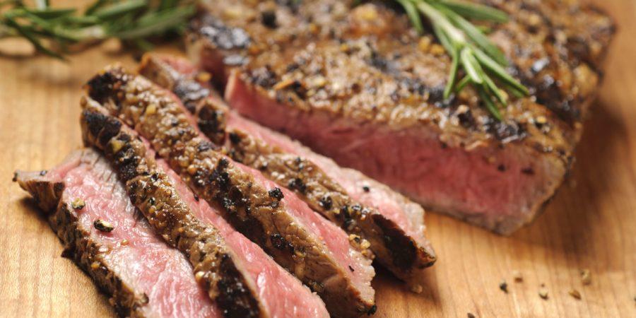 Gegrilltes Steak wird auf einem Schneidebrett in Scheiben geschnitten. Bitte sehen Sie mein Portfolio für andere lebensmittelbezogene Bilder.