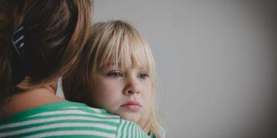 trauriges weinendes kleines Mädchen, das Mutter, Elternschaft und Schutz umarmt