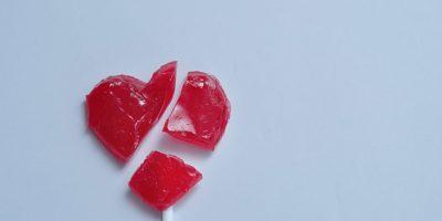 Ein gebrochenes rotes Herz-Lutscher als Symbol für ein gebrochenes Herz