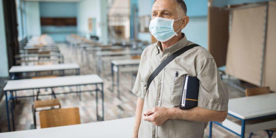 Porträt eines Professors in einem leeren Klassenzimmer mit Gesichtsmaske