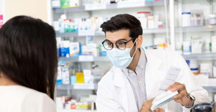 Apotheker, der eine hygienische Schutzmaske trägt und in der modernen Apotheke Medikamentenempfehlungen gibt