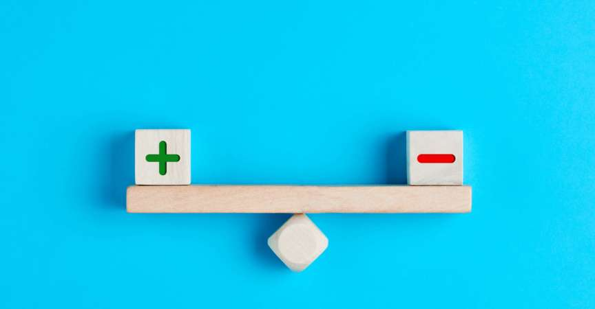 Plus und Minus oder positive und negative Symbole auf Holzklötzen sind auf einer Holzwippe im Gleichgewicht