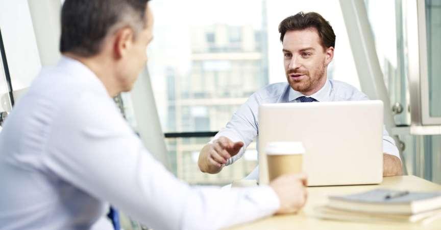 zwei kaukasische Geschäftsleute, die ein Gespräch im Büro führen.