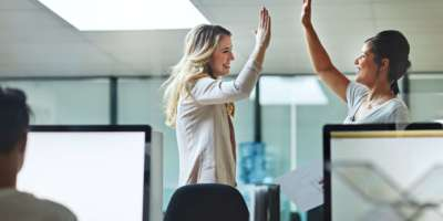 Aufnahme von zwei Kollegen, die sich bei der Arbeit ein High Five geben