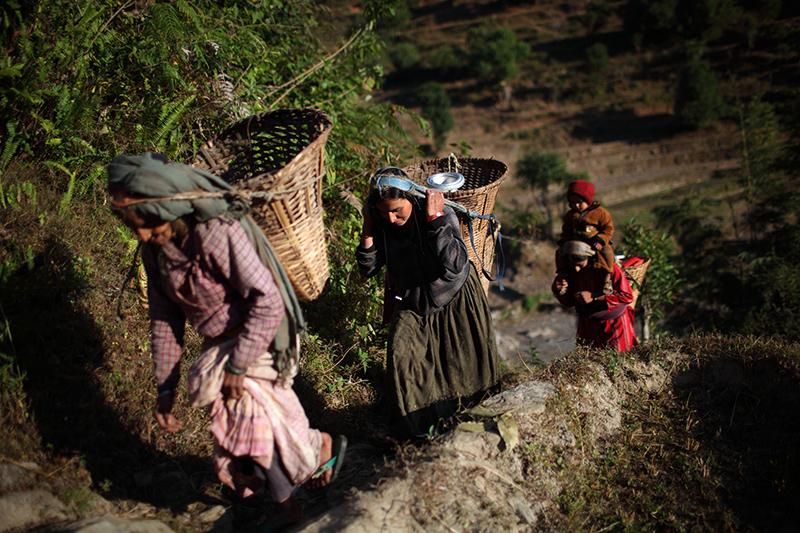 Nanuka Adhikari (leuchtend roten Kleidern, mit Baby) und Familie tragen Wasser von einer unsicheren Quelle bis einen steilen Berghang in Tosramkhola VDC, Sindhuli, Nepal, November 2011.