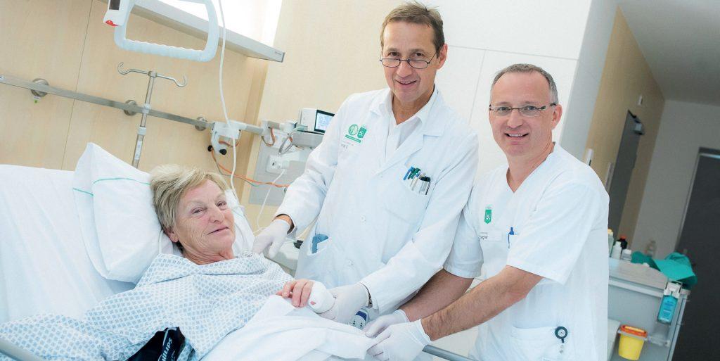 Prof. Spendel (l.) und DGKP Harald Sägner betreuen eine Patientin.