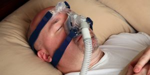 Caucasian male with sleep apnea wears a CPAP machine mask in bed.