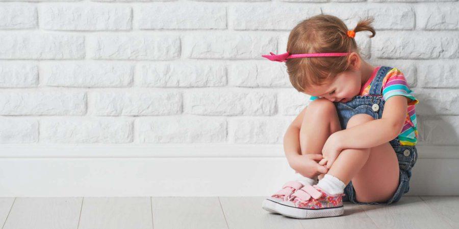 kleines Kind Mädchen weinen und traurig über eine leere Mauer