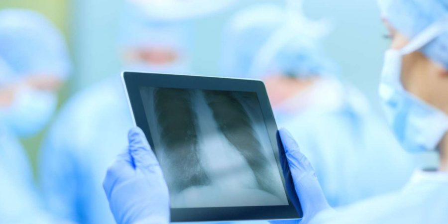 Chirurg, der Röntgen auf Tablet-Computer im Operationssaal untersucht