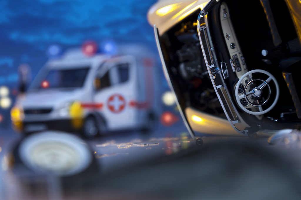 Car crash on highway at night. Ambulance in background. Focus is on the tire. Selective Focus